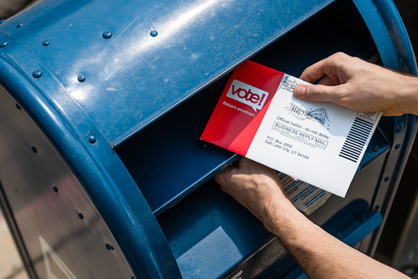 A ballot is placed in a blue postal service bin.