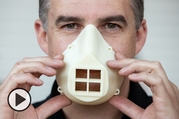 BYU employee Therin Garrett holds a 3D printed mask over his nose and mouth.