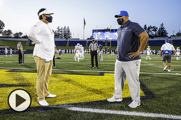 The football coaches from Navy and BYU, both wearing masks, stand in the middle of a football field, chatting.