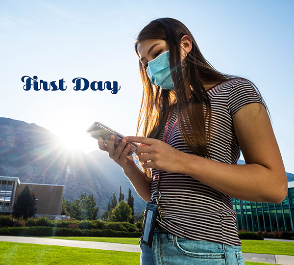 A masked female BYU student looks at her phone in front of the campus library. The sun rises over Y mountain in teh background.