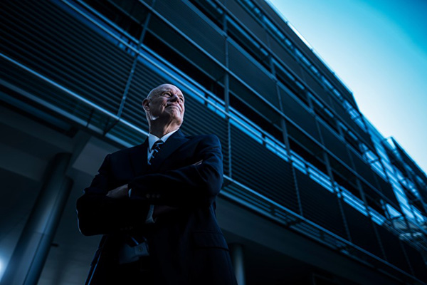 Forensic linguist William Eggington, arms folded and wearing a dark suit, stands in front of a tall building wrapped in metal railings.