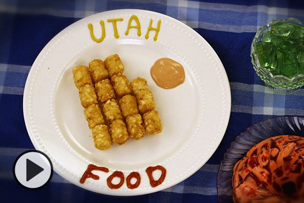 The words Utah Food are written in ketchup and mustard on a white plate with tater tots arranged in the shape of the state of Utah punctuated with a dollop of fry sauce. Two etched glass containers hold sides of green and red-orange Jello salads. A blue plaid tablecloth acts as backdrop.