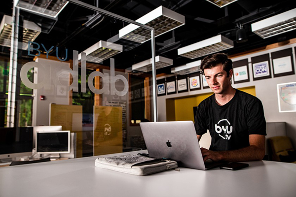 A male BYU student wearing a BYUtv tshirt sits at a computer in the AdLab on campus.