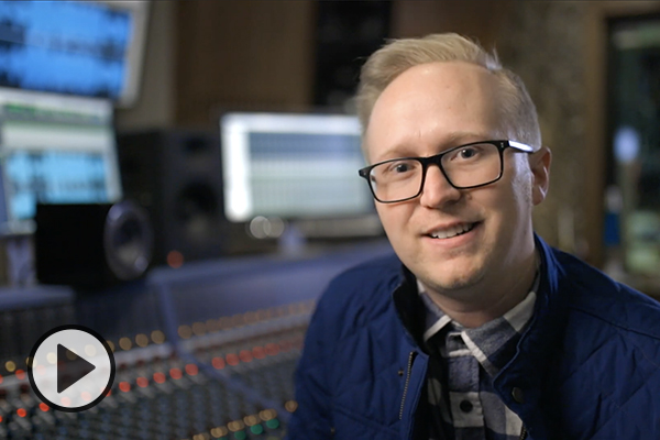 Blonde-haired, black eyeglassed male sitting at an audio mixing board in a sound studio.