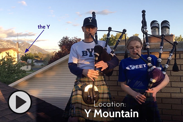 Bagpipers Jeff and Lizzie McClellan stand on the roof of their Orem home. The distant Y on Y Mountain is indicated with an arrow.