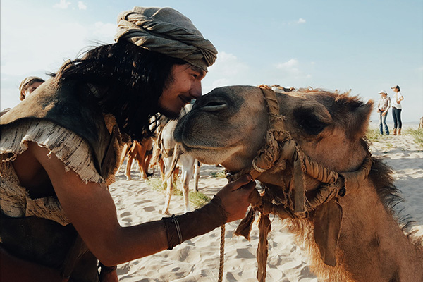 Actor Cooper Sutton touches noses with a camel on the sandy set as he works on the Book of Mormon videos.