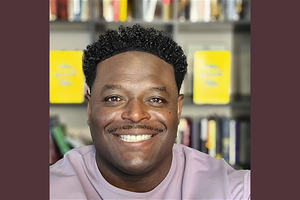 A selfie of former BYU football player and pastor Derwin Gray in front of bookshelves.