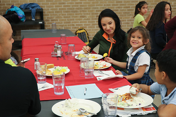 A family seated for a meal, with real plates, silverware, and a tablecloth in a school cafeteria. Caption reads: A community school like Manzano Mesa Elementary succeeds as it addresses the needs of families as well as those of children.