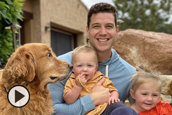Jimmer Fredette smiles big while holding two of his children. The family dog looks on.