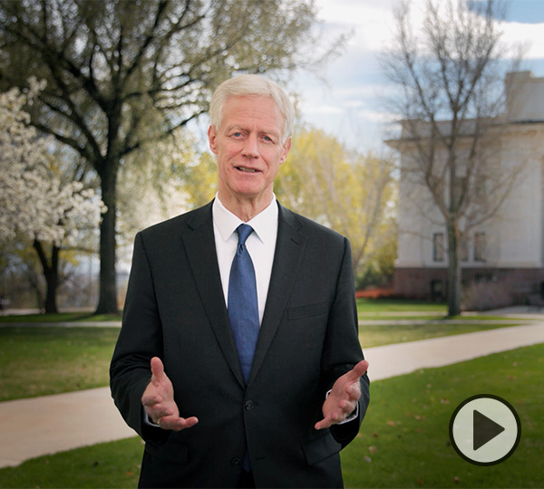 With spring blooms in the background, President Kevin J Worthen, wearing a dark suit and blue tie, hands extended, stands and speaks near a campus sidewalk leading to the Maeser Building.
