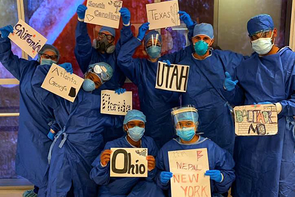 A group of nurses in New York City display signs indicating where they came from, places like Ohio, Florida, Nepal, Texas, and Utah.