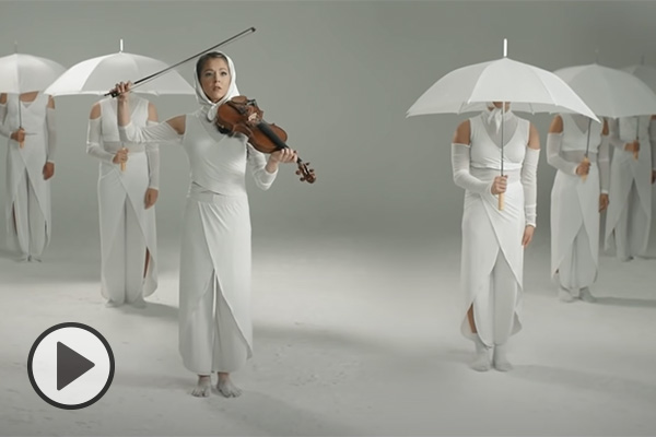 Lindsey Stirling and 5 dancers are all dressed in white dresses with white headscarves. Lindsey is holding a violin, all others hold white umnbrellas