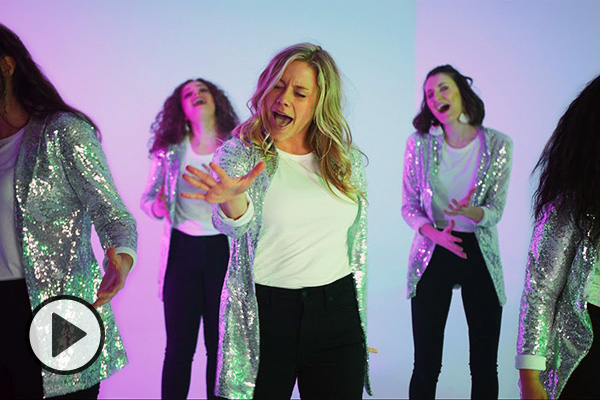 Pink- and lavender-tinted photo of BYU Noteworthy dancing, singing, and emoting. all dressed in matching sparkly silver jackets, white t-shirts, and black pants.