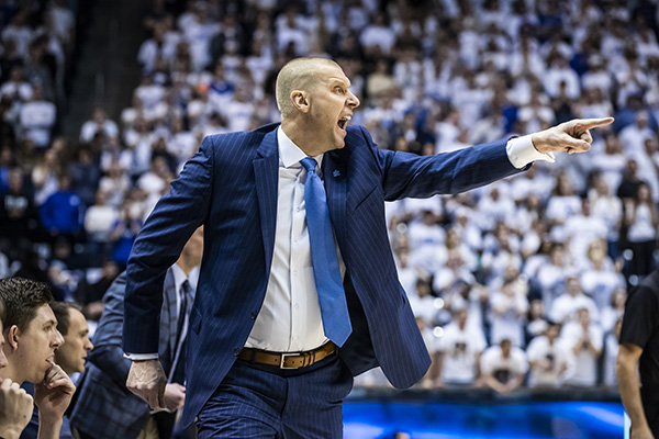 BYU head basketball coach Mark Pope points at the court, yelling instructions to either his players or a referee.