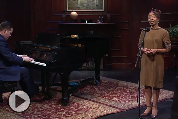 A female vocal artist sings, accompanied by a pianist.