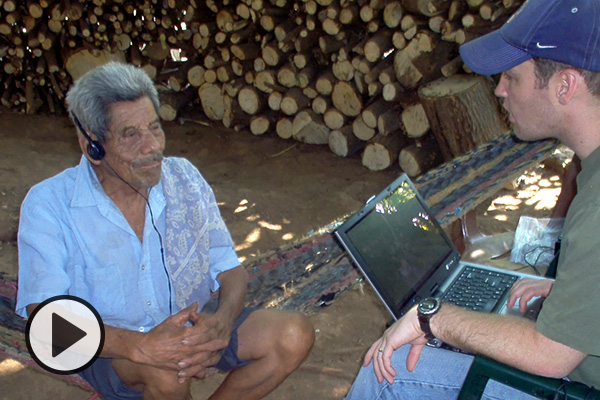 Linguistics professor Chris Rogers holding a laptop sits in a rustic hut in Guatemals, interviewing Carlos, the last speaker of the Xinkan language, who is wearing headphones.