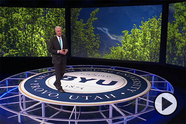BYU president Kevin J Worthen walks across a circular stage with a prominent campus medallion. Images of trees and Y Mountain are displayed on large screens behind him.