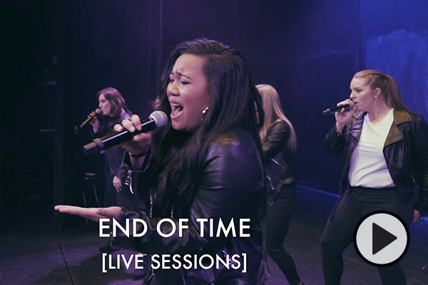 The female singers of BYU Noteworthy hold microphones and sing in unison. They wear matching leather jackets and white t-shirts as they perform on a soundstage. Text says End of Time Live Sessions.