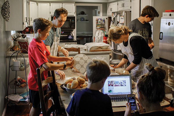 The six members of the Nielson family mill around the kitchen, busy baking and doing work on a phone and laptop.