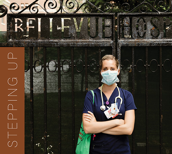 Channing Hoybjerg Voyles, a nurse at New York City's Bellevue Hospital, wears navy blue scrubs, a mask, and stethoscope and stands in front of the black metal gates of her workplace. Photo: Marilyn in New York City for Flytographer.