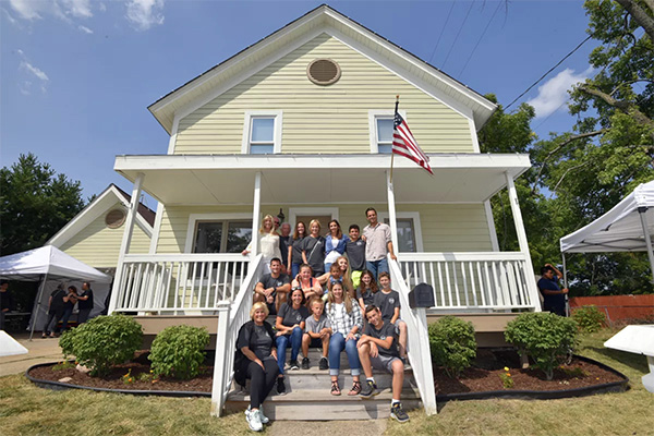 More than a dozen people pose on the front steps and white porch of a recently remodeled American home.