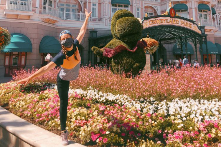 Dancer Bronwell Merrill, wearing a backwards ball cap and mask, strikes a dance pose on a flower garden wall at the Disneyland Park in Paris.