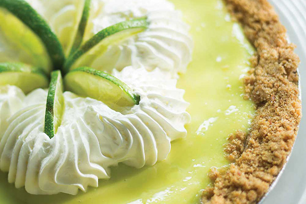 Closeup photo of a lime pie garnished with lime slices and whipped cream.