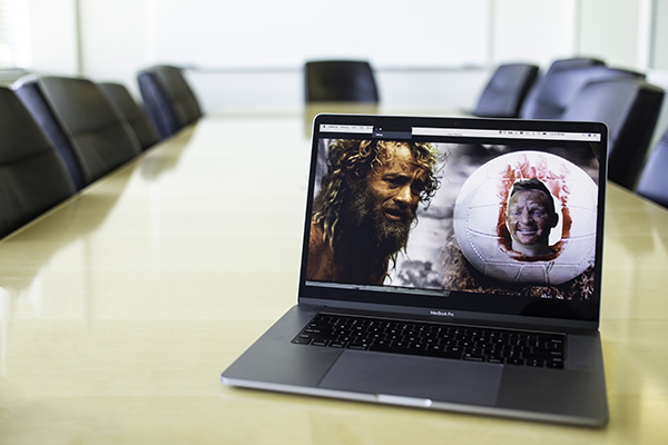 On a laptop, MBA student Trevor Lemmons is shown in a Zoom meeting as Wilson, the volleyball, from Castaway next to a back ground of actor Tom Hanks in his supporting role as a stranded survivor.